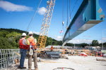 Workers on the eastbound span roadway watch the installation of the project's final girder.
